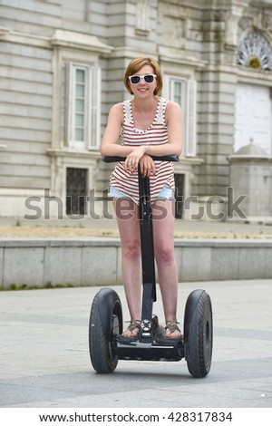 young attractive tourist woman with red hair wearing shorts and summer singlet riding happy electrical segway having fun driving in touristic city tour in Madrid royal palace in Spain - stock photo