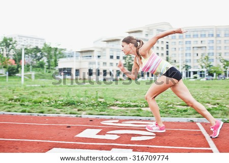 Young attractive trained blonde woman athlete in bright sportswear runs outdoors on running path of her university campus stadium. Dynamic photo with motion blur with focus on model
