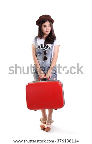 Young attractive traveler woman standing  with red suitcase, looking sideways waiting for her ride, full length isolated on white background - stock photo