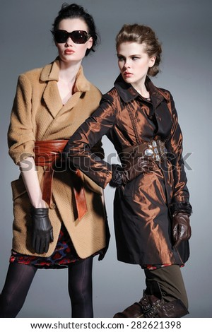 young attractive two girl wearing coat on gray background  - stock photo
