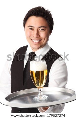 Young attractive waiter wearing a white shirt and black waistcoat, serving a nice cold beer. White background. - stock photo