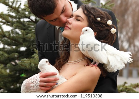 Young attractive wedding couple with pigeons pair, broom kiss bride over park autumn outdoor - stock photo