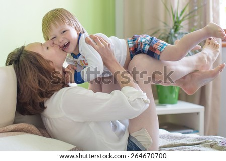 Young attractive woman and her child have fun indoor - stock photo