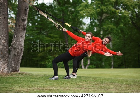 Young attractive woman and man do suspension training with fitness straps or trx outdoors in nature. Group of people training simultaneously.