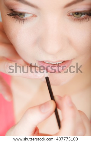Young attractive woman applying lipstick on lips. Pretty gorgeous girl beautifying. Make up. - stock photo