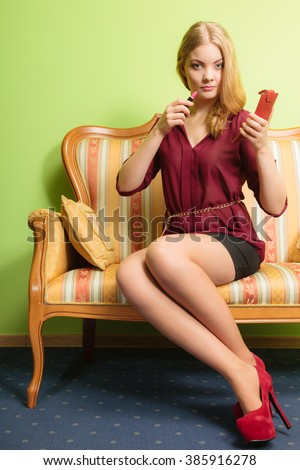 Young attractive woman applying lipstick on lips. Pretty gorgeous girl sitting on vintage retro sofa couch. Fashion and make up. - stock photo