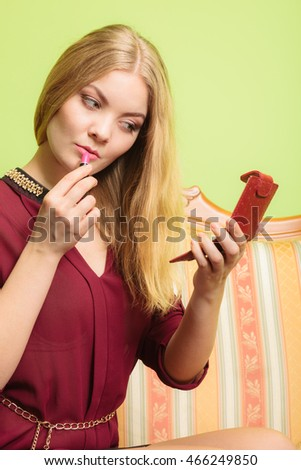 Young attractive woman applying lipstick on lips. Pretty gorgeous girl sitting on vintage retro sofa couch. Fashion and make up.