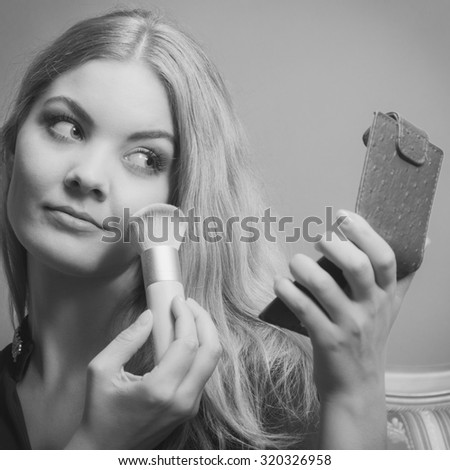 Young attractive woman applying make up with powder brush. Pretty gorgeous girl beautifying. Fashion and makeup. Black & white photo. - stock photo