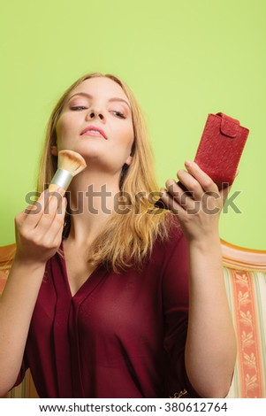 Young attractive woman applying make up with powder brush. Pretty gorgeous girl beautifying. Fashion and makeup. - stock photo