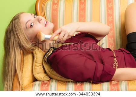 Young attractive woman applying make up with powder brush. Pretty gorgeous girl laying on vintage retro sofa couch. Fashion and makeup. - stock photo