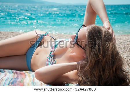 Young attractive woman at summer beach in swimsuit