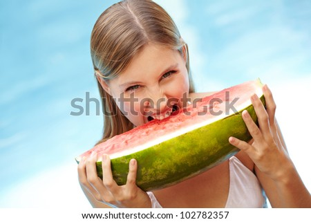 Young attractive woman biting in watermelon in swimming pool