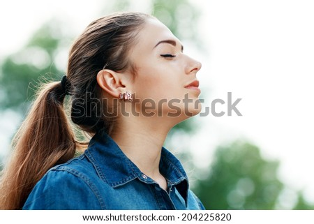 Young attractive woman breathing fresh air outdoors showing his face to the wind  - stock photo