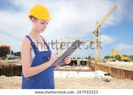 young attractive woman builder writing something in clipboard at construction site