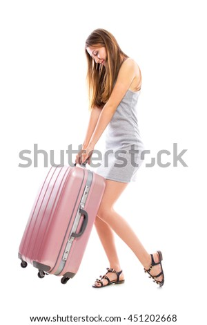 Young attractive woman carries a heavy suitcase isolated on white background. - stock photo