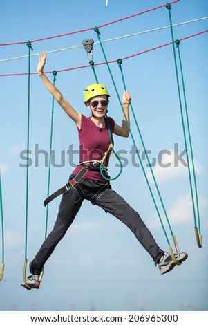 Young attractive woman climbing in adventure rope park in mountain helmet and safety equipment over blue sky background - stock photo