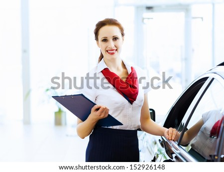 Young attractive woman consultant of car center standing near car - stock photo