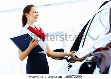 Young attractive woman consultant of car center standing near car
