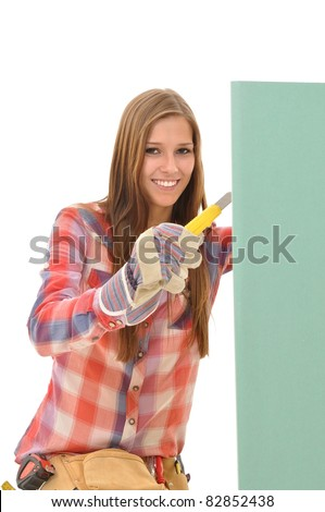 Young attractive woman cutting a green gypsum board - stock photo