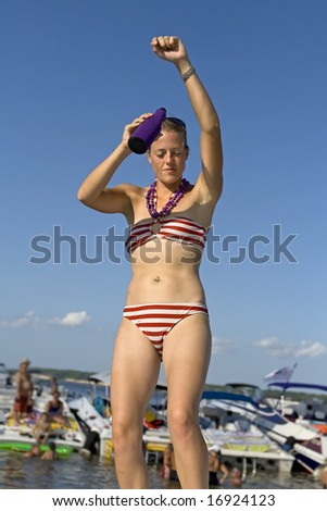 Young attractive woman dancing in a red and white striped bikini.