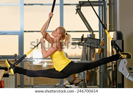 Young attractive woman does splits crossfit stretching with trx fitness straps in the gym's studio