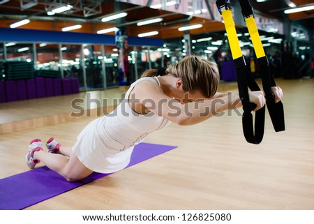 Young attractive woman does suspension training with fitness straps in the gym's studio - stock photo