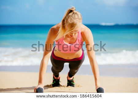 Young attractive woman doing push ups outside with barbells. Fitness woman working out at the beach. Fitness Concept. - stock photo