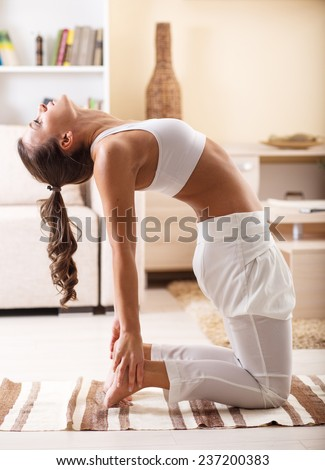 Young attractive woman doing yoga in her living room.Natural light ambient.