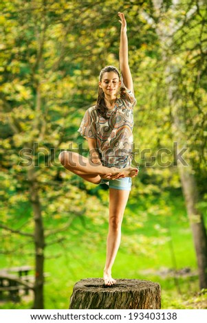 Young attractive woman doing yoga in nature. - stock photo