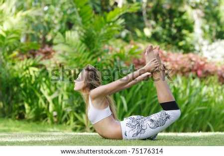 young attractive woman doing yoga on natural background