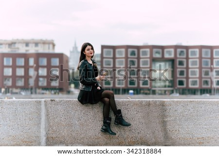 Young attractive woman dressed in classy clothes posing while sitting outdoors with mobile phone, gorgeous female tourist using cell telephone while rest after walking outside during her autumn trip - stock photo