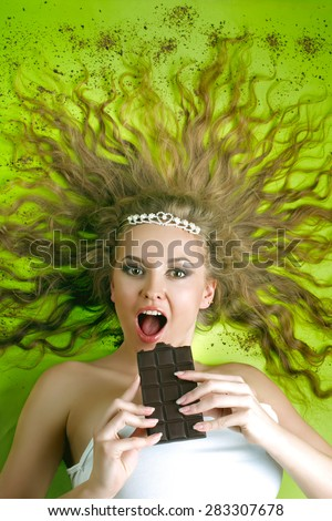 Young attractive woman eating chocolate - stock photo