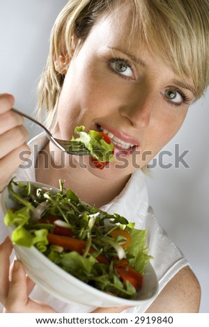 young attractive woman eating salad close up - stock photo