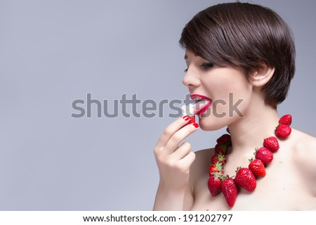 young attractive woman eating strawberry with cream