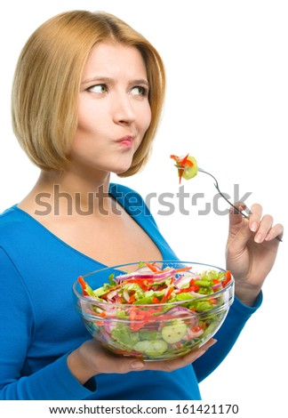 Young attractive woman eats vegetable salad using fork and making funny grimace, isolated over white