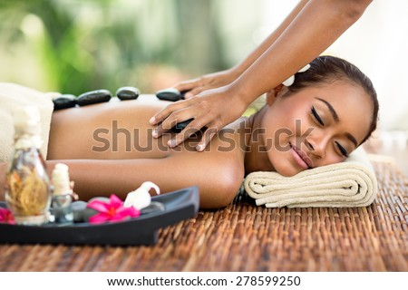 Young attractive woman enjoying in professional Asian massage back - stock photo