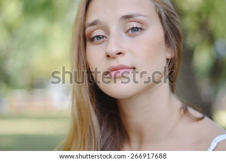 Young attractive woman, enjoying nature on summer day outside in park. Summer girl portrait.   - stock photo