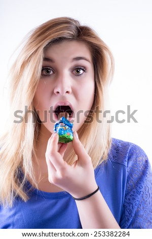 Young attractive woman feels caught when eating their chocolate rabbit - stock photo