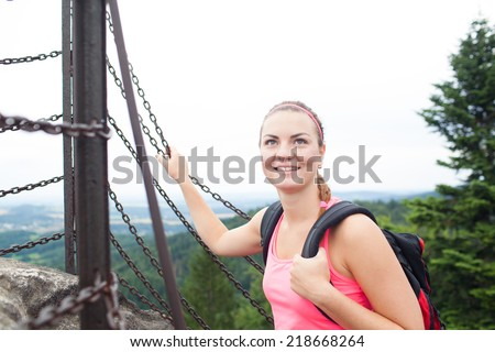Young attractive woman/female tourist on the top of the hill/moutain/rock looking around on beautiful landscape (shallow DOF) - stock photo
