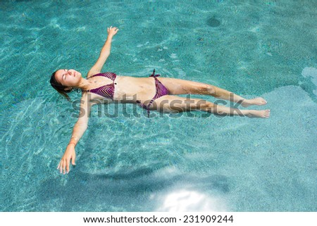 Young attractive woman floating in the swimming pool with eyes closed