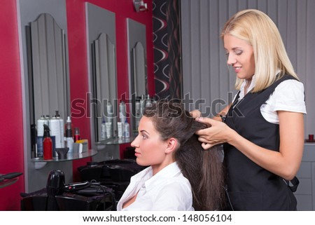 young attractive woman getting a new haircut by hairdresser at barbershop - stock photo