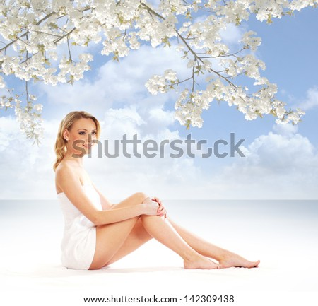 Young attractive woman getting spa treatment over resort background - stock photo