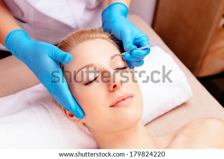 Young attractive woman having her eyebrows done at a beauty shop - stock photo