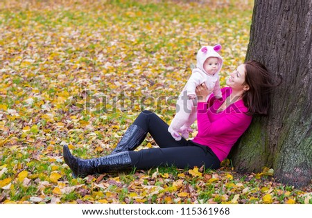 Young attractive woman holding a baby sitting under a tree on yellow and orange leaves - stock photo