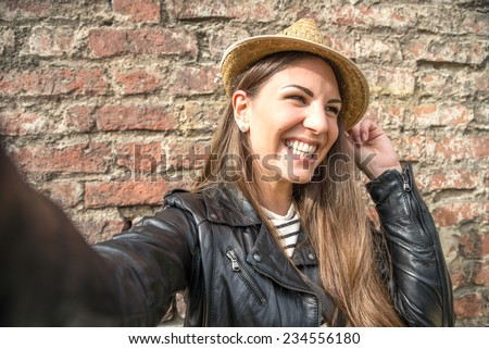 Young attractive woman holding a camera and taking a self portrait with funny face - stock photo