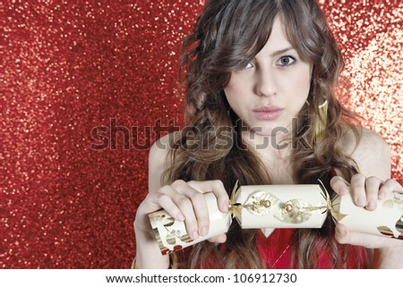Young attractive woman holding and pulling a Christmas cracker against a red glitter background. - stock photo