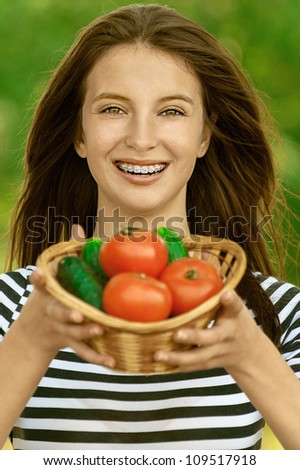 Young attractive woman holding basket of tomatoes and cucumbers, against green of summer park. - stock photo