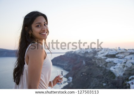 Young attractive woman holding champagne flute over scenic background