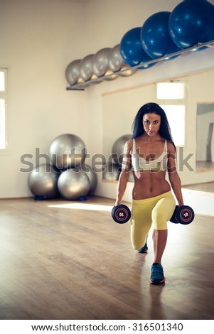 Young attractive woman holding dumbbells. Selective focus.