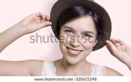 Young attractive woman holding her hat and smiling - stock photo